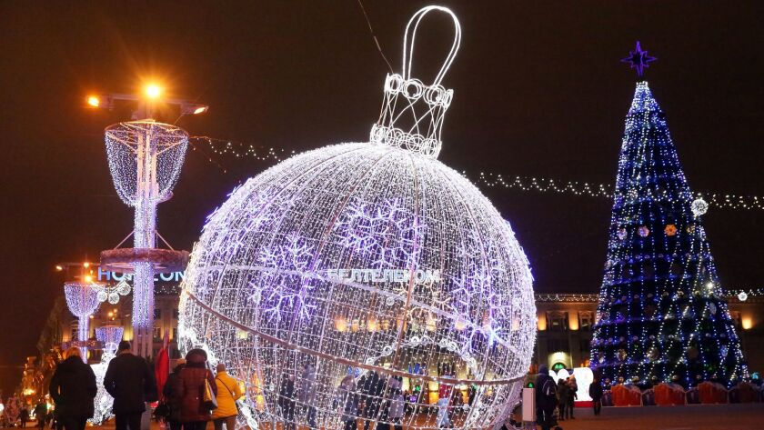 People walk past giant illuminated holiday ornaments at Octyabrskaya Square in Minsk, Belarus on Dec. 18.
