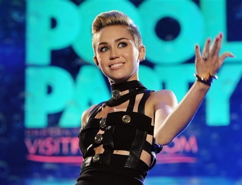 """FILE - This June 29, 2013 file photo shows Miley Cyrus hosting the iHeartRadio Ultimate Pool Party at the Fontainebleau Hotel in Miami. Cyrus' song, """"We Can't Stop,"""" is one of the top songs of the summer for the Teen Choice Awards, airing Sunday, Aug. 11. (Photo by Jeff Daly/Invision/AP, File)"""