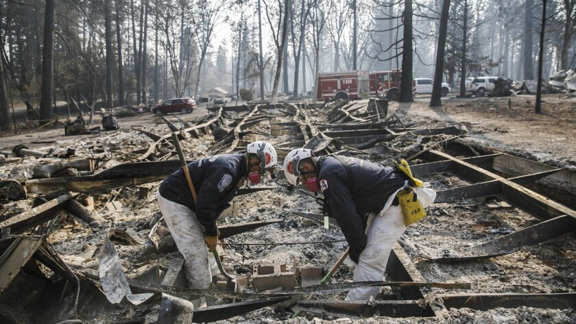 A search team Tuesday carefully scans an area for human remains after the Camp fire destroyed most of Paradise, Calif.