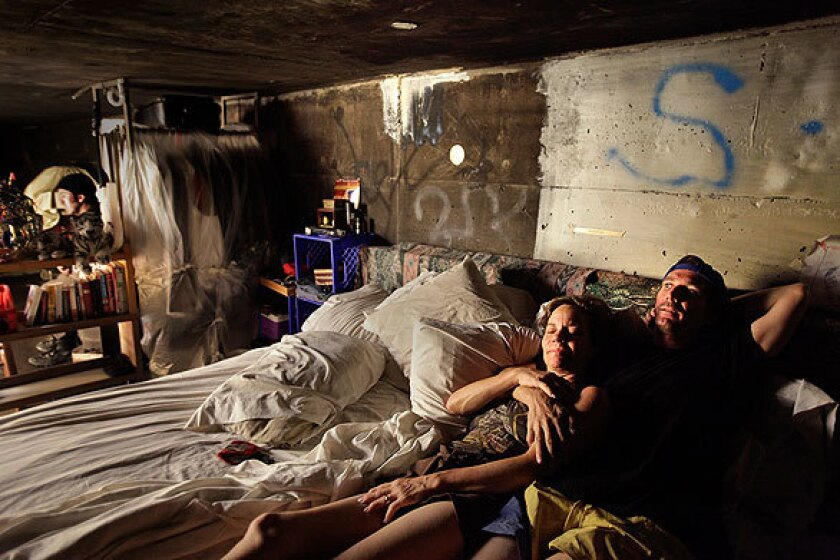 Steve, right, and his girlfriend Kathryn (they asked that their last names and ages not be used) lie in their large bed in a storm drainage tunnel under the city of Las Vegas. The pair, who have one of the more elaborate encampments among the tunnel-dwellers, have many of the comforts of a real home, but lack electricity and running water.