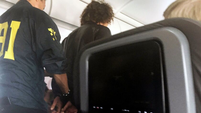In a photo provided by a passenger, a man is escorted off an American Airlines flight upon arrival in Honolulu.