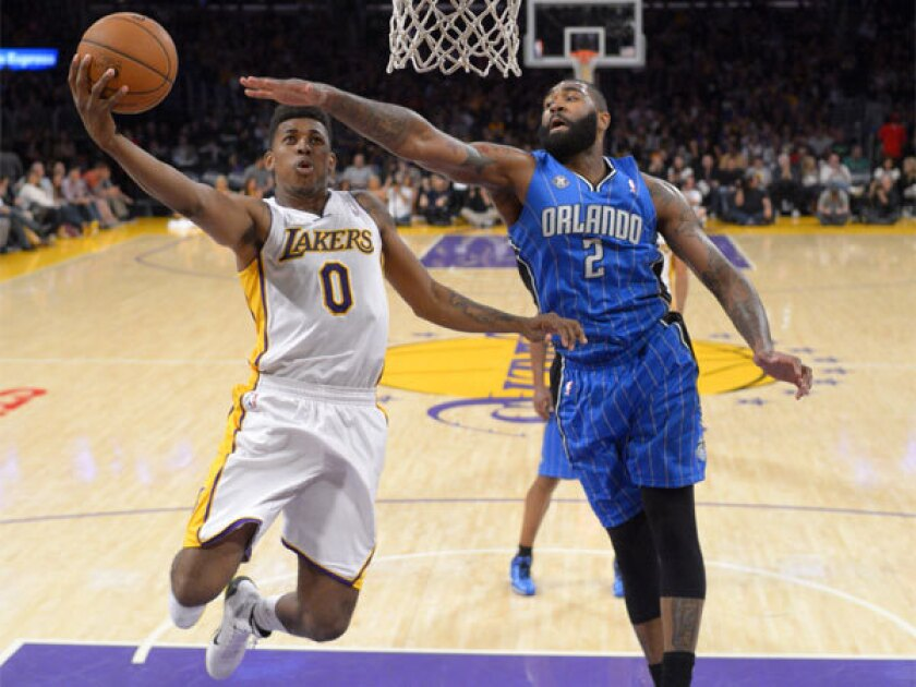 Lakers forward Nick Young, left, puts up a shot against Orlando forward Kyle O'Quinn at Staples Center on Sunday night.