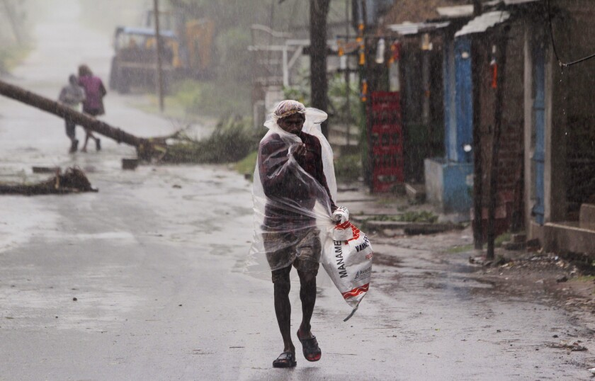 A man walks in the rain ahead of Cyclone Amphan's making landfall May 20 in the eastern Indian state of Orissa.
