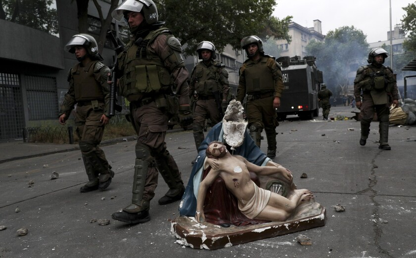 Police advance on anti-government protesters, past a religious statue that protesters removed from a church and then damaged, in Santiago, Chile, Friday, Nov. 8, 2019. Chile's president on Thursday announced measures to increase security and toughen sanctions for vandalism following three weeks of protests that have left at least 20 dead. (AP Photo/Esteban Felix)