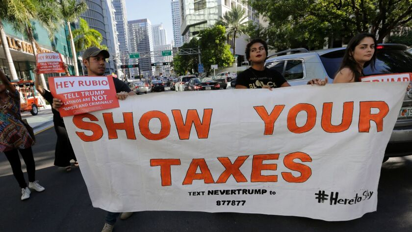 Marching protesters in Miami hold up a sign demanding that then-candidate Donald Trump release his tax returns.