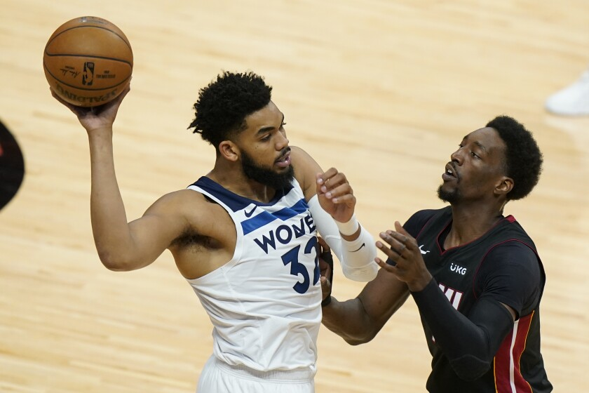 Minnesota Timberwolves center Karl-Anthony Towns (32) looks for an open teammate past Miami Heat center Bam Adebayo during the first half of an NBA basketball game, Friday, May 7, 2021, in Miami. (AP Photo/Wilfredo Lee)