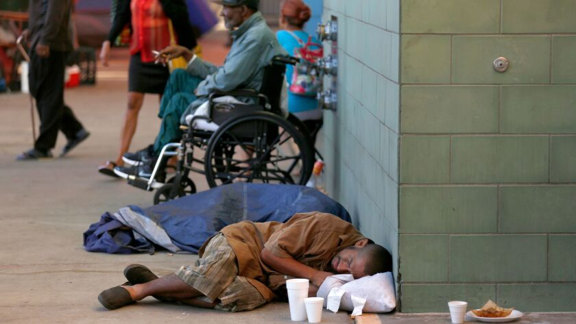 A man sleeps on the sidewalk in front of the Union Rescue Mission on skid row in downtown L.A. last month.