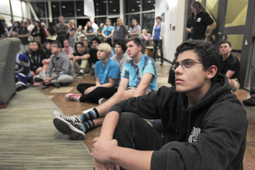 An overflow crowd of spectators fills the Poway school district office lobby as they watch the school board meeting on video monitors.