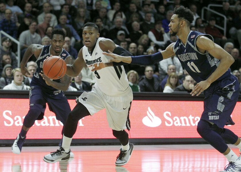 Providence guard Kris Dunn (3) drives to the basket as Georgetown guard L.J. Peak, left, and forward Isaac Copeland (11) defend during the first half of an NCAA college basketball game in Providence, R.I., Saturday, Feb. 13, 2016. (AP Photo/Stew Milne)