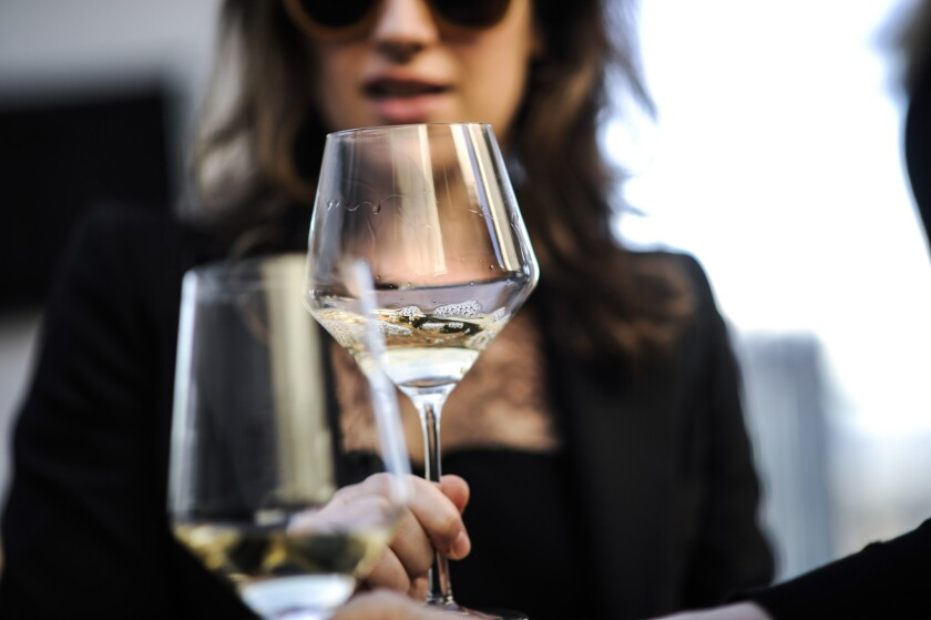 Women clink wine glasses at an event.