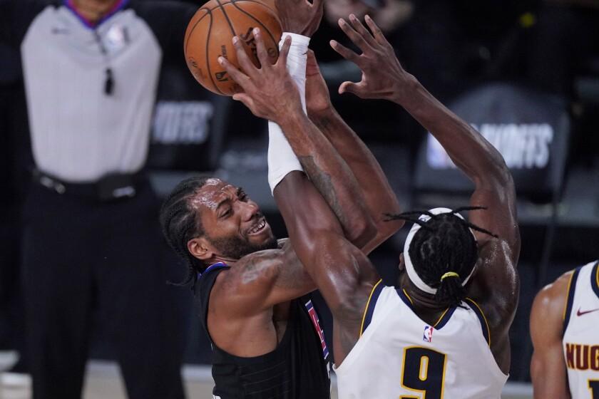 Clippers forward Kawhi Leonard is defended by Denver Nuggets forward Jerami Grant.
