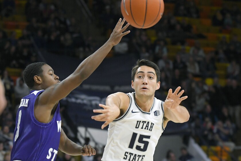 Utah State guard Abel Porter (15) passes the ball away from Weber State guard KJ Cunningham during an NCAA college basketball game Friday, Nov. 8, 2019, in Logan, Utah. (AP Photo/Eli Lucero)