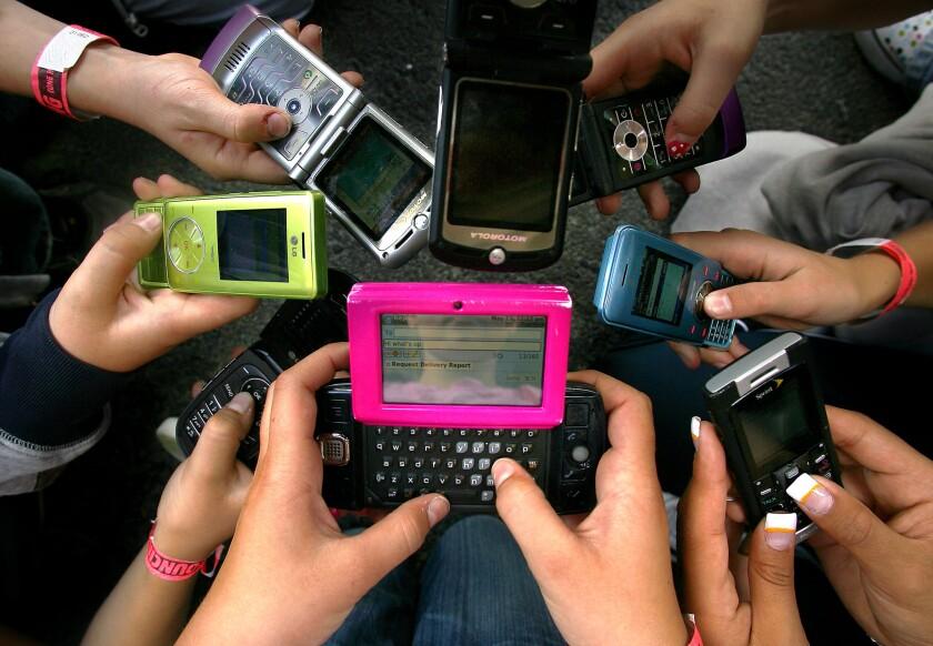 Granite Elementary School sixth-grade students hold up their cellphones in Sandy, Utah, in 2008. (AP Photo/Deseret News, Kristin Murphy)