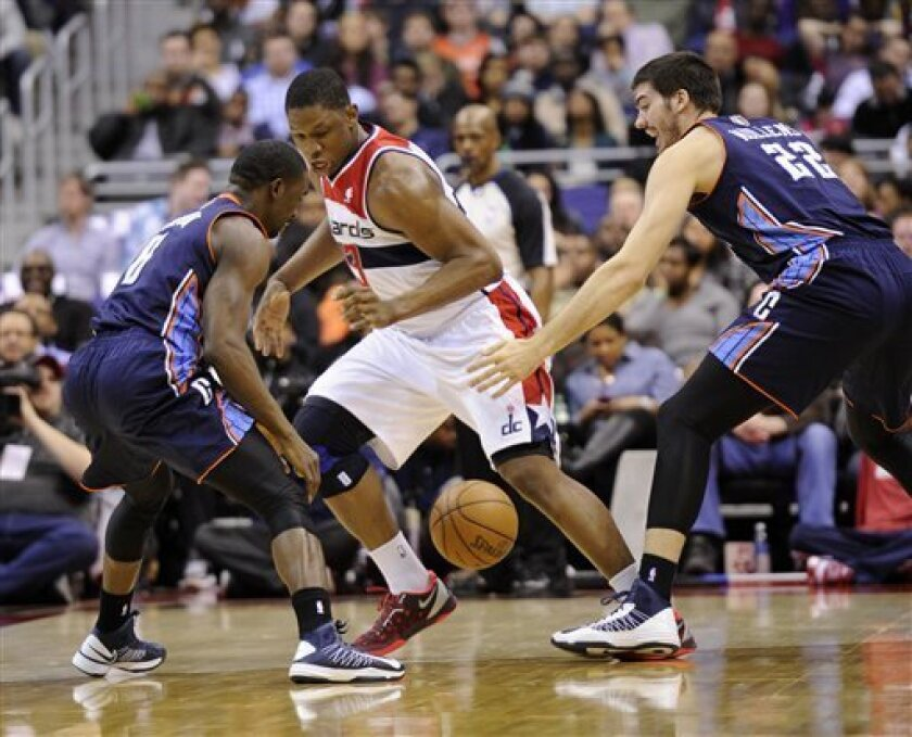 Charlotte Bobcats' Ben Gordon, left, and Byron Mullens (22) look for the loose ball against Washington Wizards forward Kevin Seraphin, center, during the first half of an NBA basketball game, Saturday, March 9, 2013, in Washington. (AP Photo/Nick Wass)