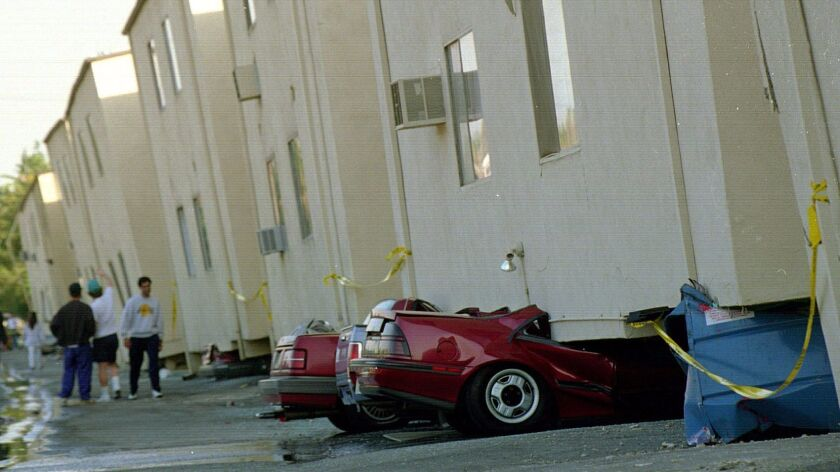Cars sit underneath a collapsed apartment building after the 1994 Northridge earthquake.