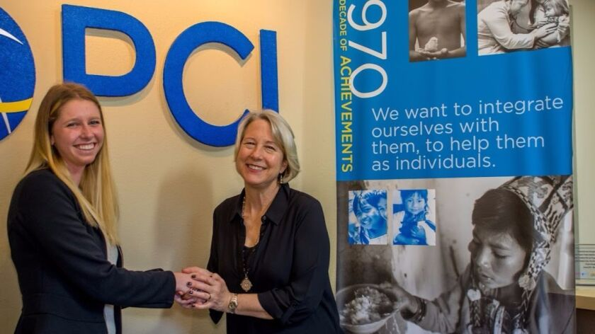 Carrie Hessler-Radelet (right), the new president and CEO of Project Concern International, recently paid her first official visit to the aid organization's San Diego headquarters to meet employees. She greets staff member Katie Fiorillo by the PCI logo.