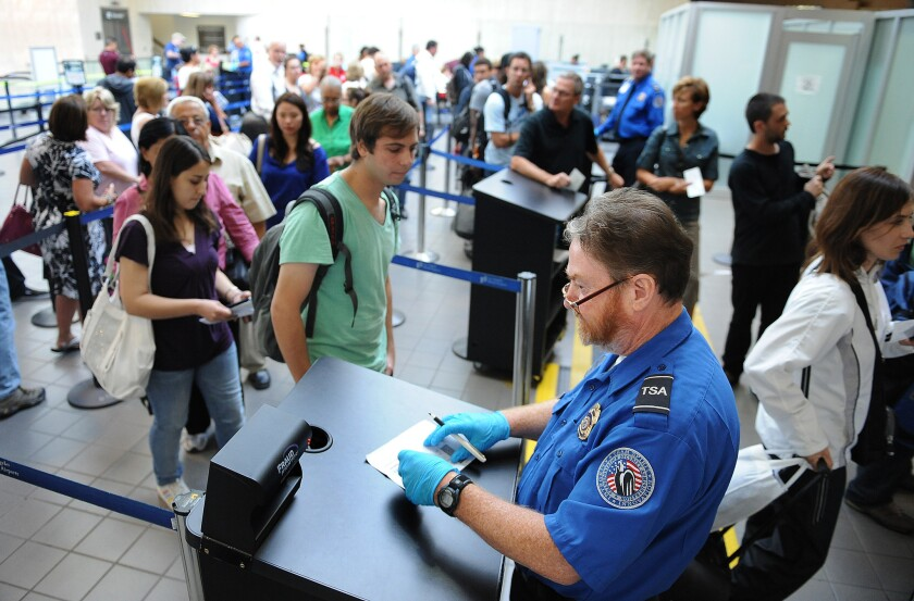 A TSA agent checks the identification of travelers at Los Angeles International Airport. The TSA is offering the public cash for ideas to speed up screening lines.