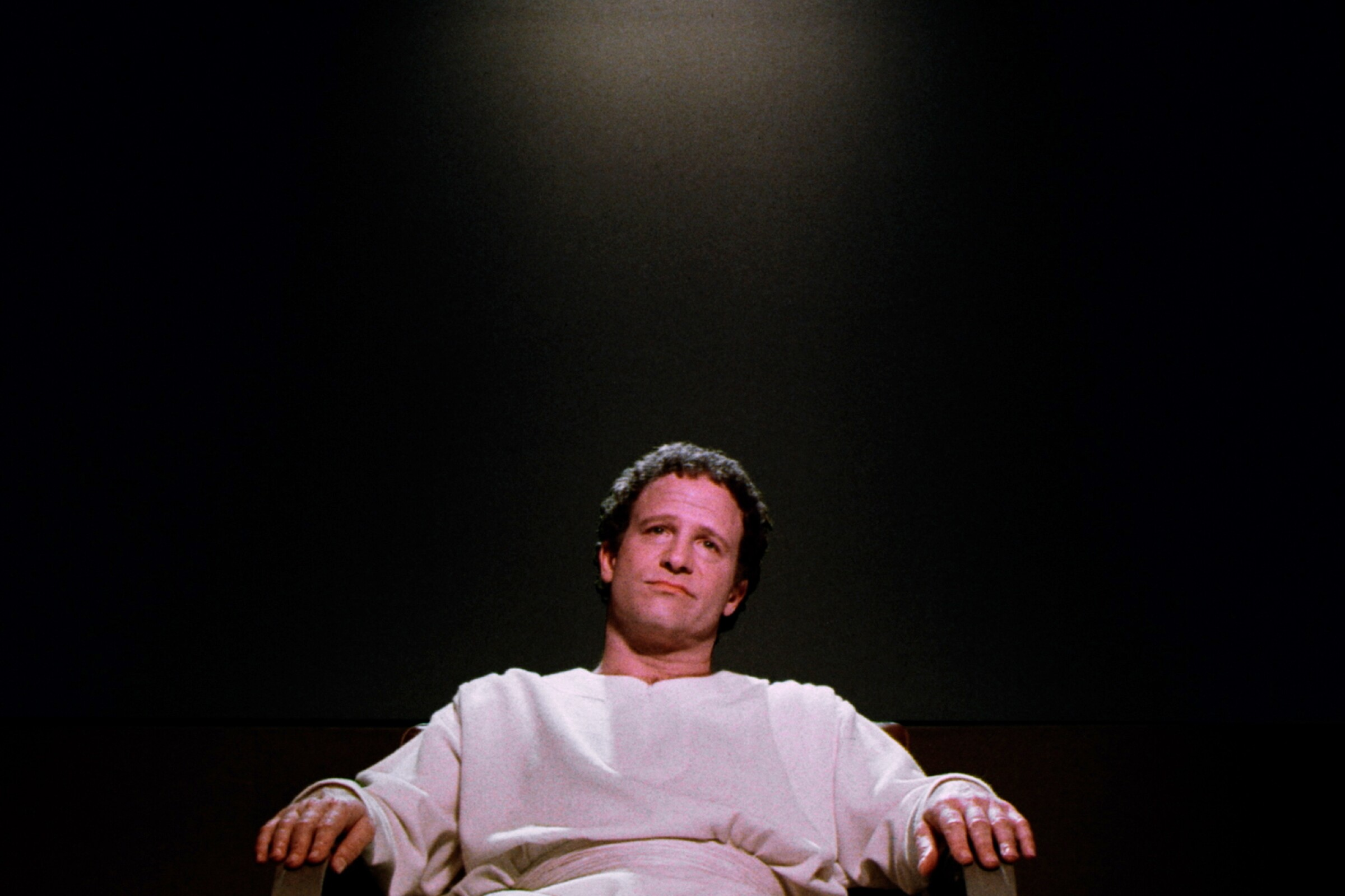 """Albert Brooks sitting in a chair in """"Defending Your Life."""""""