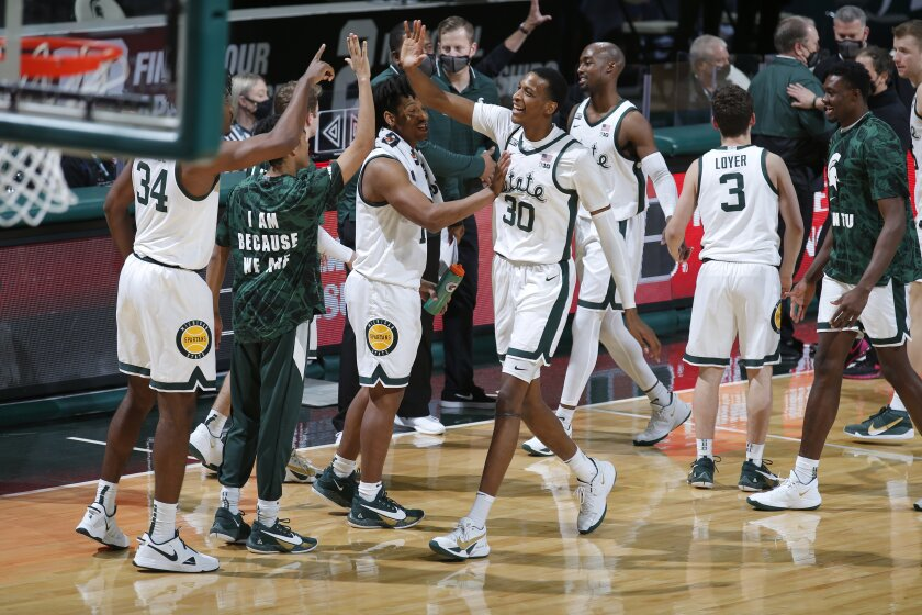 Michigan State players celebrate following their win over Penn State in an NCAA college basketball game, Tuesday, Feb. 9, 2021, in East Lansing, Mich. Michigan State won 60-58. (AP Photo/Al Goldis)