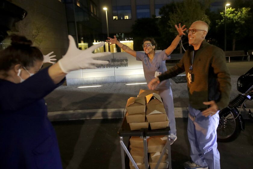 La propietaria del Nightbird Restaurant Kim Alter (izq) abraza a la distancia a la enfermera Sydney Gressel