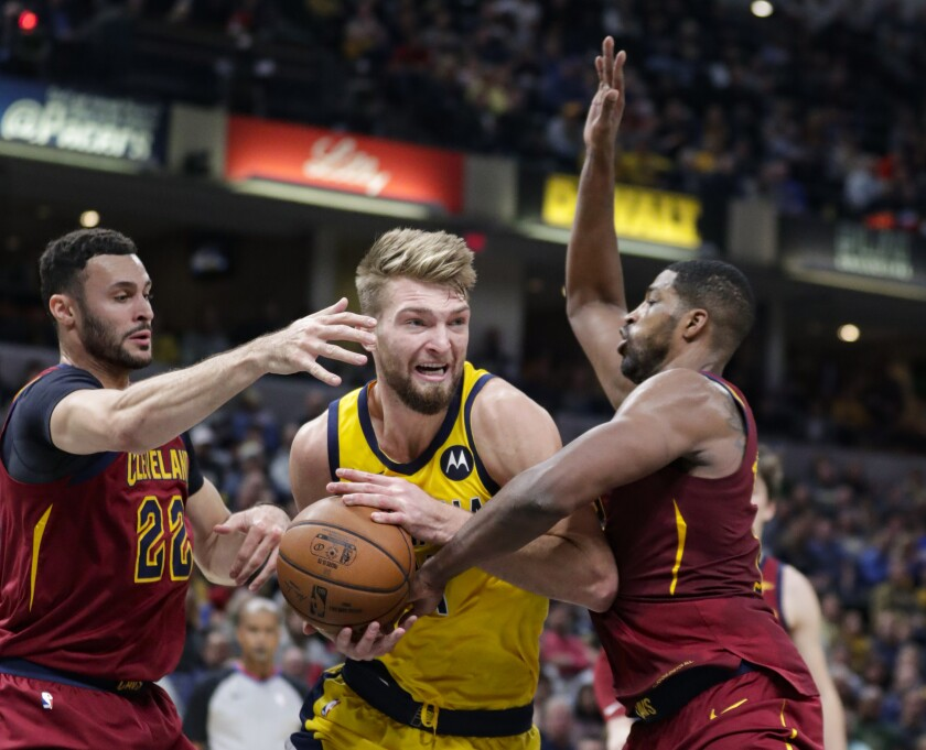 Indiana Pacers forward Domantas Sabonis (11) tries to shoot between Cleveland Cavaliers forward Larry Nance Jr. (22) and center Tristan Thompson during the first half of an NBA basketball game in Indianapolis, Friday, Nov. 1, 2019. (AP Photo/Michael Conroy)