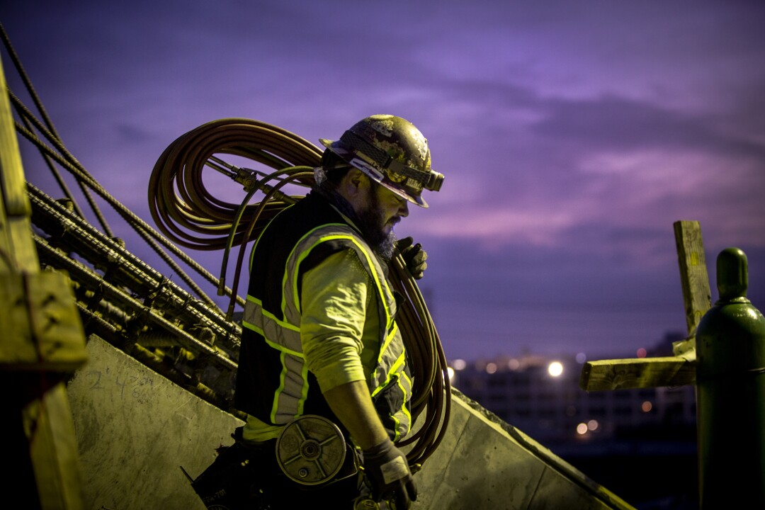 A construction worker carries a coil of cable on his shoulder