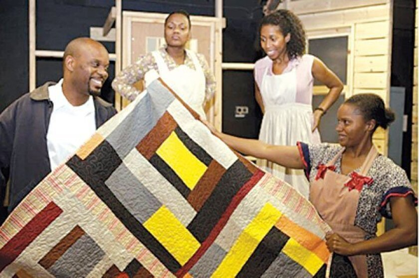 Gee's Bend cast members pose with a quilt from the play.