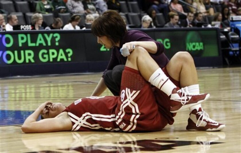 Oklahoma's guard Morgan Hook is tended to by a trainer after getting hit during a drive against Tennessee during the regional semifinal in the women's NCAA college basketball tournament in Oklahoma City, Sunday, March 31, 2013. (AP Photo/Alonzo Adams)