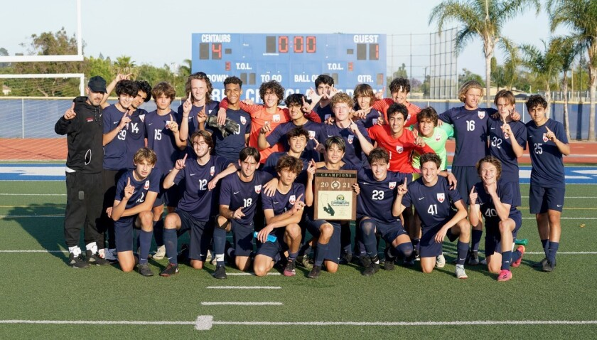 Players gather on a soccer field for a team picture. One player holds a large plaque.