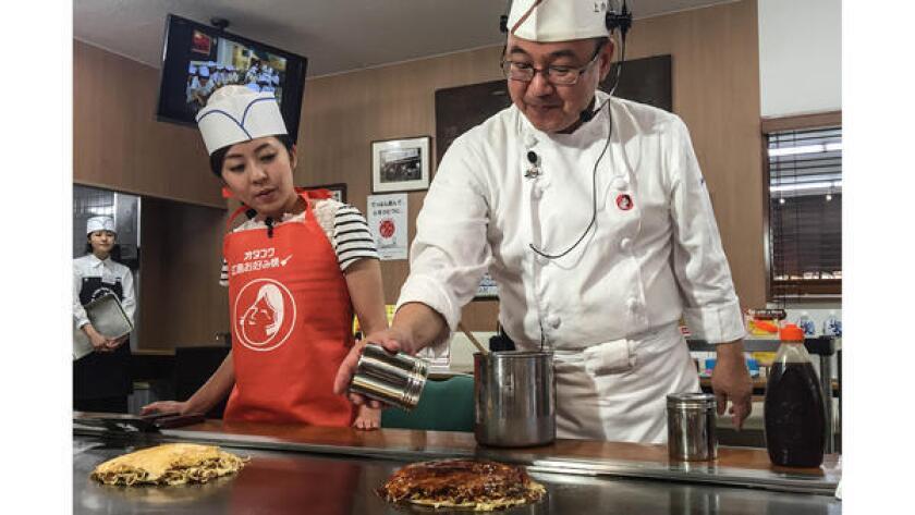 Yoshihiro Ueuchi enseña a los visitantes cómo preparar okonomiyaki.