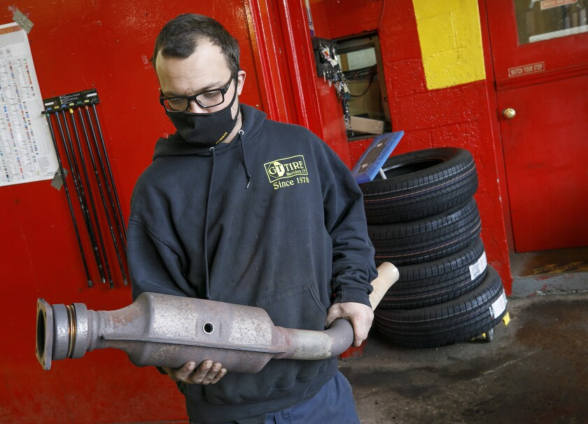 In this Feb. 5, 2021 file photo, Ari Thielman, manager at GT Tire & Service Center, holds a catalytic converter.