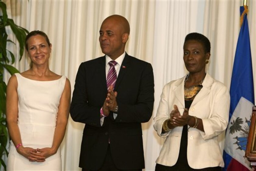 Haiti's President Michel Martelly is flanked by Haiti's new goodwill ambassadors, actress Maria Bello, left, and former government official Danielle Saint Lot at a ceremony in their honor at the National Palace in Port-au-Prince, Haiti, Tuesday, Oct. 23, 2012. Saint Lot is a longtime women's activist and Bello is the co-founder of women's grassroots group We Advance. (AP Photo/Dieu Nalio Chery)