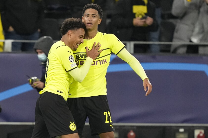 Dortmund's Donyell Malen, left, celebrates with Dortmund's Jude Bellingham after scoring his side's opening goal during the Champions League Group C soccer match between Borussia Dortmund and Sporting CP Lisbon, in Dortmund, Germany, Tuesday, Sept. 28, 2021. (AP Photo/Martin Meissner)
