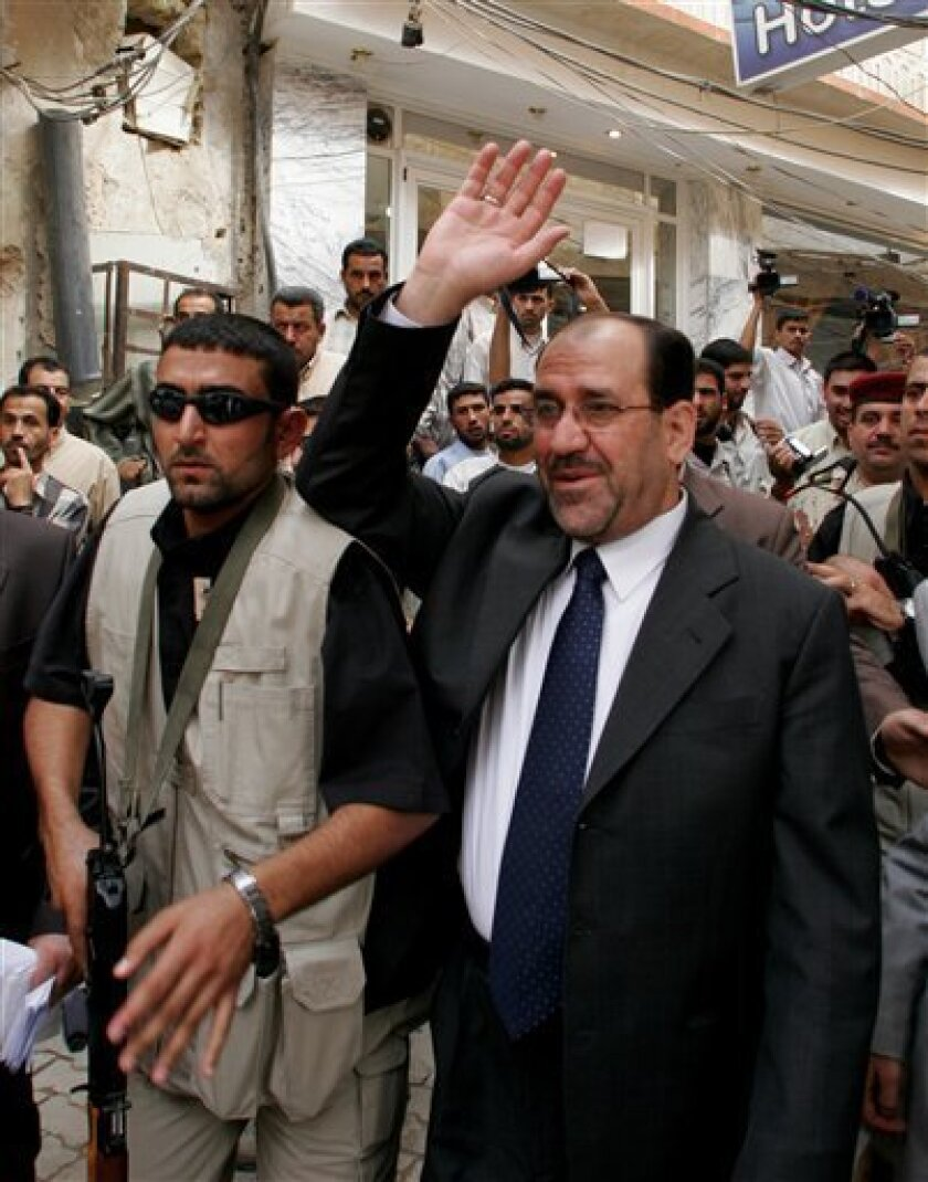 FILE - In this Oct. 18, 2006 file photo, Iraqi Prime Minister Nouri al-Maliki walks through central Najaf, 160 kilometers (100 miles) south of Baghdad. Aides to Shiite cleric Muqtada al-Sadr say his powerful political bloc has agreed to support the Iraqi prime minister's bid to stay in power and end a nearly seven-month political impasse. The backing of al-Sadr would push the Shiite-led coalition of Nouri al-Maliki close to the needed parliamentary majority to form a new government. Iraq has been in political limbo since March elections, won by a Sunni-backed bloc but without enough seats to oust al-Maliki.(AP Photo/Alaa al-Marjani, File)