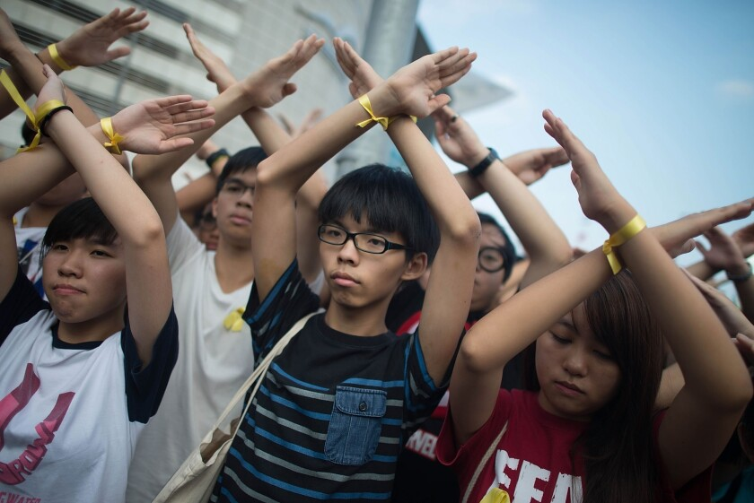 Joshua Wong, center, and other protesters turn their backs and raise crossed hands in silence at a flag-raising ceremony at Golden Bauhinia Square in Hong Kong.