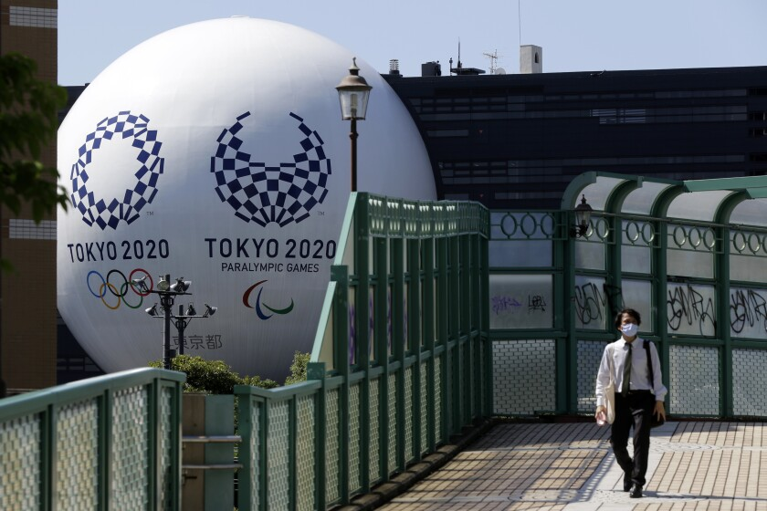 A man wearing a mask walks on a pedestrian bridge over the train tracks Wednesday, Sept. 9, 2020, in Tokyo as a large display of Tokyo 2020 Olympics and Paralympics games are seen in the background. (AP Photo/Kiichiro Sato)