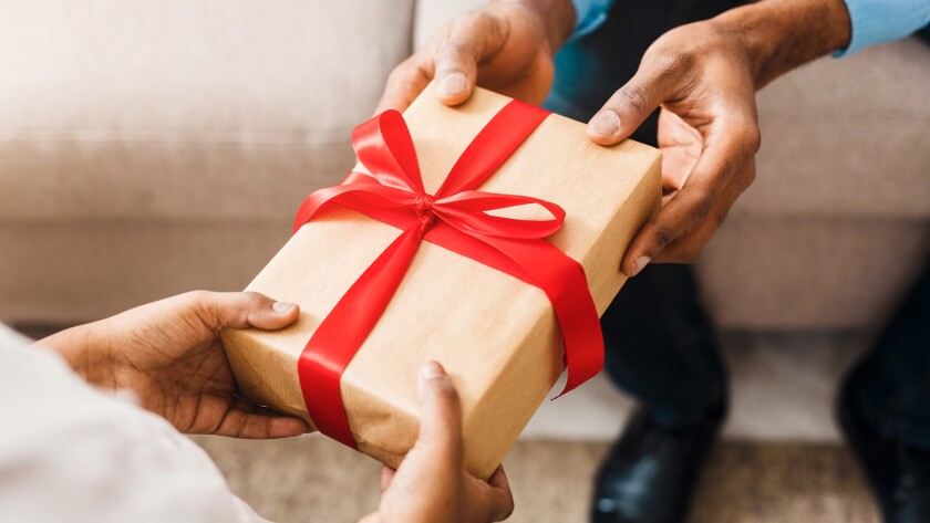 Birthday present. Father giving gift to daughter, closeup