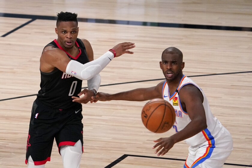 Rockets guard Russell Westbrook makes a pass under pressure from Thunder guard Chris Paul durina game Sept. 2, 2020.