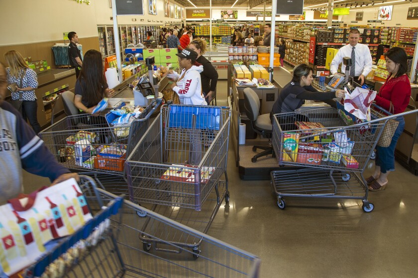 Shoppers pay for groceries at Aldi in Moreno Valley in this March file photo.