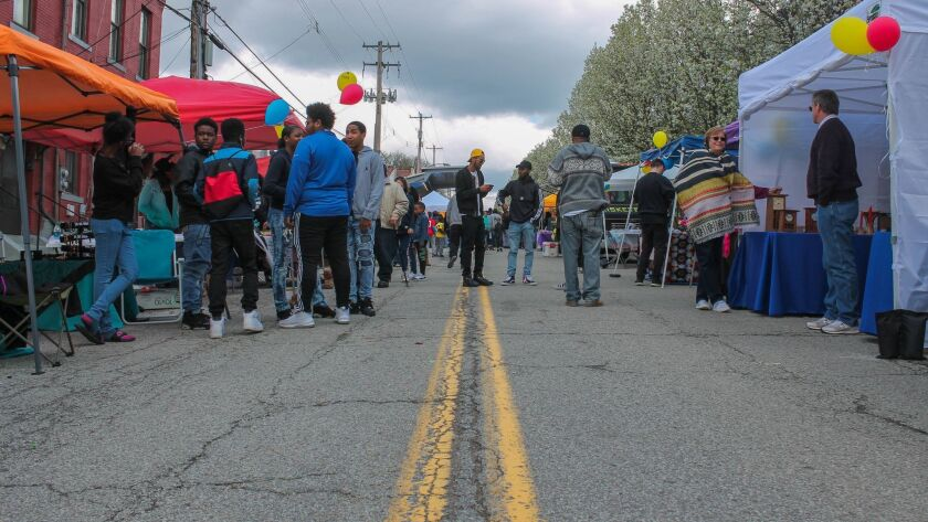 """People gather for an August Wilson block party honoring the legendary playwright in front of his long-empty childhood home at 1727 Bedford Ave. in the Hill District, the Pittsburgh neighborhood made famous in his 10-play """"Century Cycle."""""""