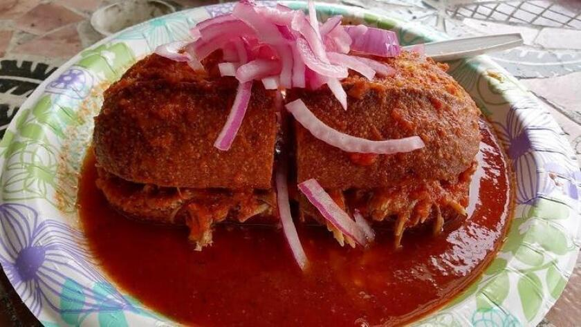 The classic torta ahogada made with birote bread, lean roasted pork, chile de arbol sauce and pickled onions. (Amy T. Granite)