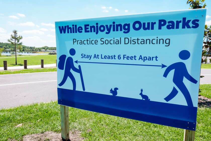 sign in park of covid-19 social distancing requirements