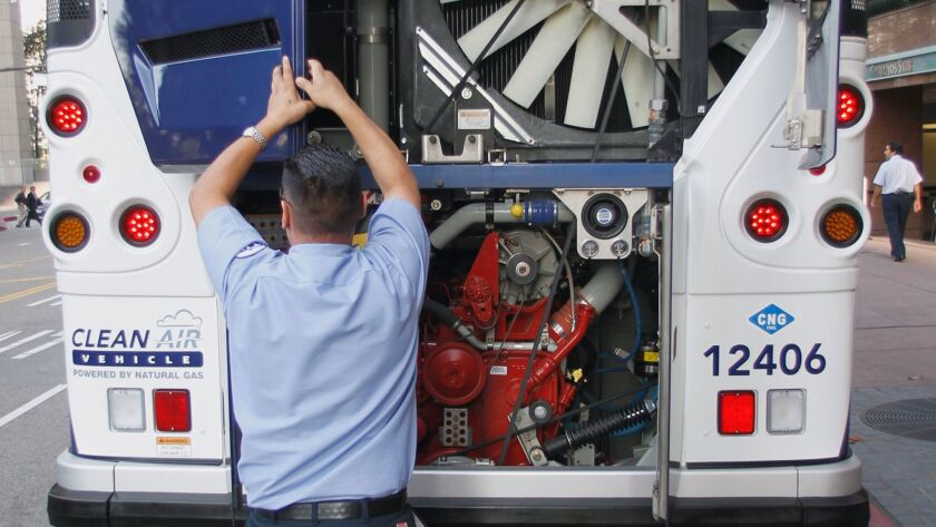 ––L.A. Metro bus operator Francisco Sigala displays the engine and cooling system for a CNG–-powered bus in Los Angeles on Nov. 30, 2011.