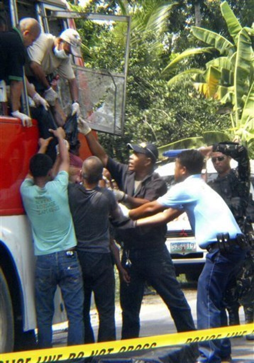 Rescuers and police investigator help pull out the body of one of bus passengers after an explosion Thursday, Oct. 21, 2010 in Matalam town in southern Philippines. A bomb ripped through the passenger bus killing at least eight people and wounding 10 in an attack authorities blamed on an extortion