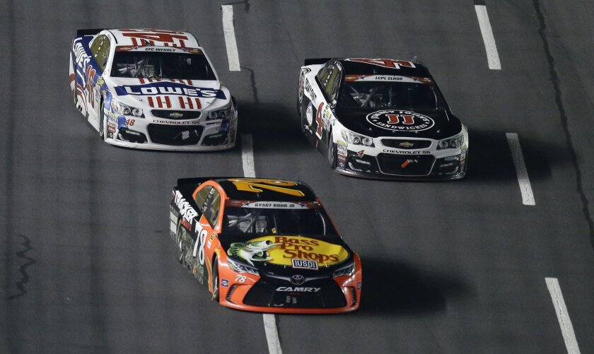 Martin Truex Jr. (78) leads Jimmie Johnson, left, and Kevin Harvick (4) following a restart late in the NASCAR Sprint Cup Series auto race at the Charlotte Motor Speedway in Concord, N.C., Sunday, May 29, 2016. True Jr. won the race. (AP Photo/Gerry Broome)