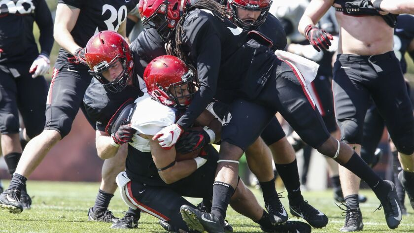 Aztecs linebacker Caden McDonald, left, and safety Dwayne Johnson Jr. combine to tackle running back Chance Bell in the second half.