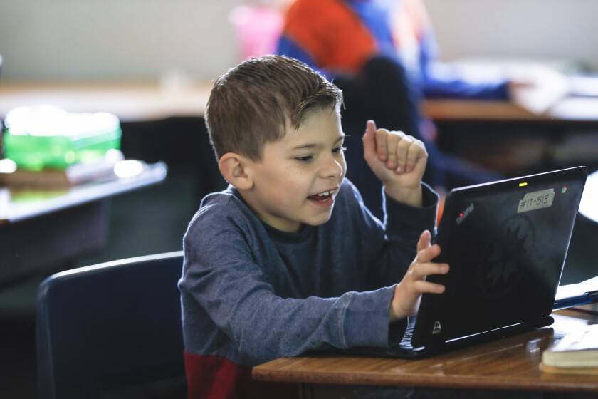 Fifth grader Johnny Moore, 10 from Perkins Elementary School, uses a laptop in February.
