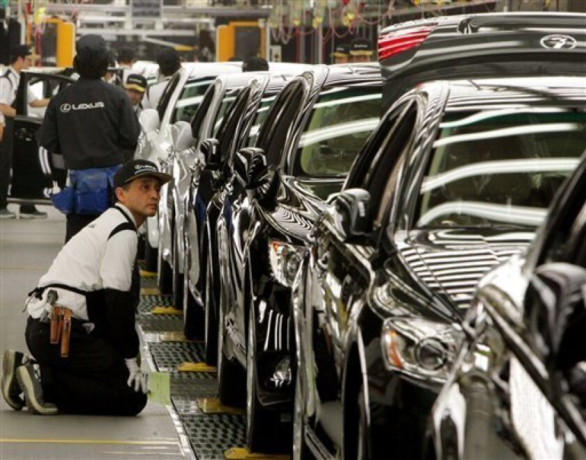 In this June 28, 2007 file photo, a Toyota Motor Corp. worker kneels down to check a Lexus at the Japanese automaker's flagship production line for luxury Lexus models in Tahara, central Japan. Toyota said Tuesday, Jan. 6, 2009 it will suspend production at all of its Japanese plants for a total o