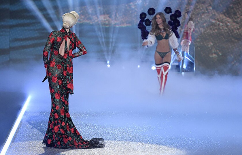 Facing away from the camera, Lady Gaga, left, performs at the 2016 Victoria's Secret Fashion Show in Paris.