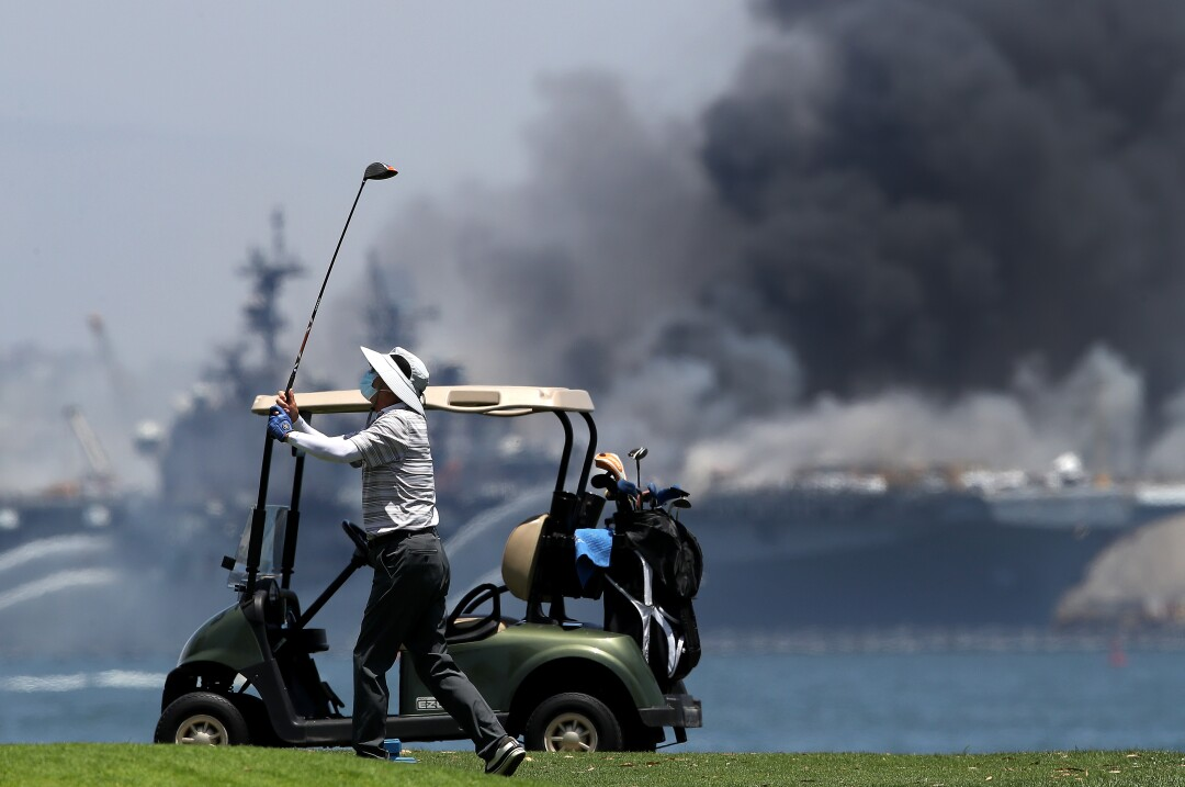 A golfer plays on as a fire burns on the amphibious assault ship USS Bonhomme Richard at Naval Base San Diego.